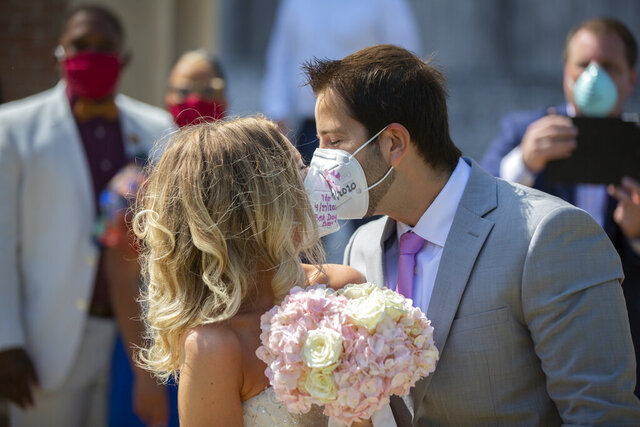 Gabrielle Schmees, 29, and Diego Grassano, 31, kiss wearing protective masks on the day of their wedding at the Gerald D. Hines Waterwall Park on Monday, April 27, 2020, in Houston.Because of COVID-19, the couple decided to postpone their official wedding and have a small one at the Waterwall Park until December when they can have the official one with all of their family and friends. (Marie De Jesus/Houston Chronicle via AP)