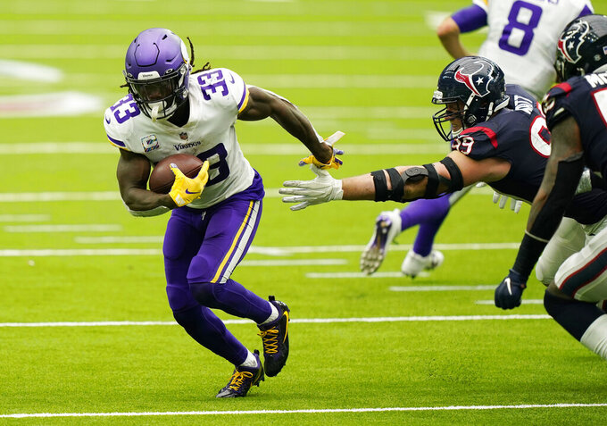 Minnesota Vikings running back Dalvin Cook (33) breaks away from Houston Texans defensive end J.J. Watt (99) during the second half of an NFL football game Sunday, Oct. 4, 2020, in Houston. (AP Photo/David J. Phillip)