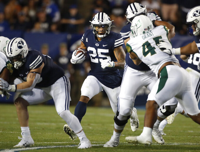 BYU running back Tyler Allgeier (25) looks for a hole as he runs the ball while South Florida defensive lineman Darrien Grant (45) fights off a block in the first half of an NCAA college football game Saturday, Sept. 25, 2021, in Provo, Utah. (AP Photo/George Frey)