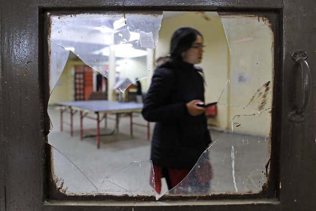 A student is seen through broken glass as she walks inside the hostel canteen room vandalized after Sunday's assault by masked assailants at the Jawaharlal Nehru University in New Delhi, India, Monday, Jan. 6, 2020. More than 20 people were injured in the attack opposition lawmakers are trying to link to the government. (AP Photo/Altaf Qadri)