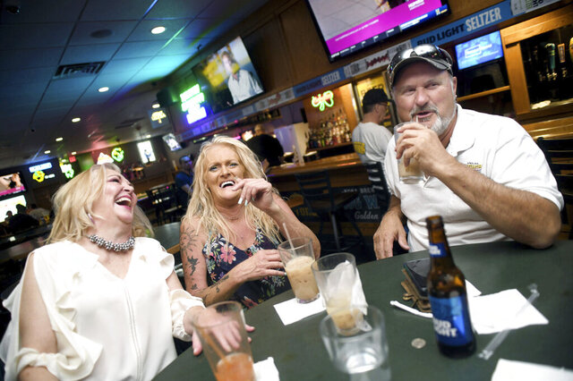 Tama Reisenauer, left, Julie Paul and Jerry Traub sit at a table at O'Brian's Sports Tavern in Bismarck, N.D., on June 19, 2020.