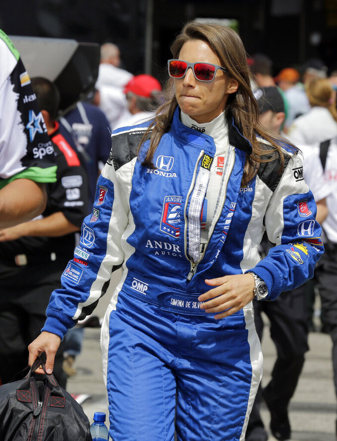 FILE - In this Friday, March 27, 2015, file photo, Simona de Silvestro, of Switzerland, walks to her car before practice for the IndyCar Firestone Grand Prix of St. Petersburg auto race in St. Petersburg, Fla. Beth Paretta and Simona de Silvestro will be teaming up to put another woman on the Indianapolis 500 starting grid this May. On Tuesday, Jan. 19, 2021, Paretta Autosport and IndyCar officials announced they would work together to put a predominantly women-run team in the series' biggest race as part of an outreach to create more diversity in motorsports. (AP Photo/Chris O'Meara, File)