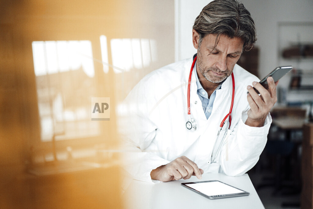 Male healthcare worker using digital tablet while leaning on desk in clinic