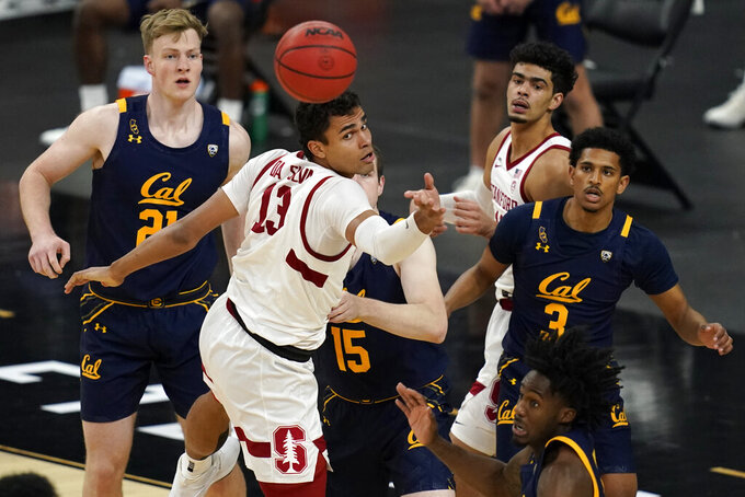Stanford's Oscar da Silva (13) tips a rebound away from California players during the first half of an NCAA college basketball game in the first round of the Pac-12 men's tournament Wednesday, March 10, 2021, in Las Vegas. (AP Photo/John Locher)