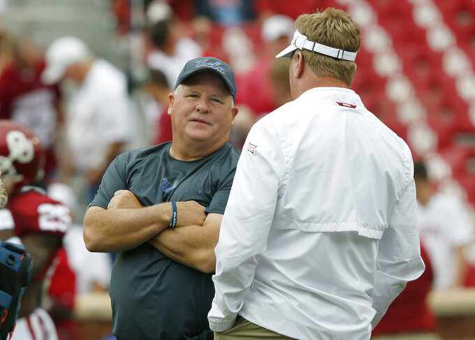 UCLA head coach Chip Kelly, left, talks with Oklahoma defensive coordinator Mike Stoops, right, before their NCAA college football game in Norman, Okla., Saturday, Sept. 8, 2018. (AP Photo/Sue Ogrocki)