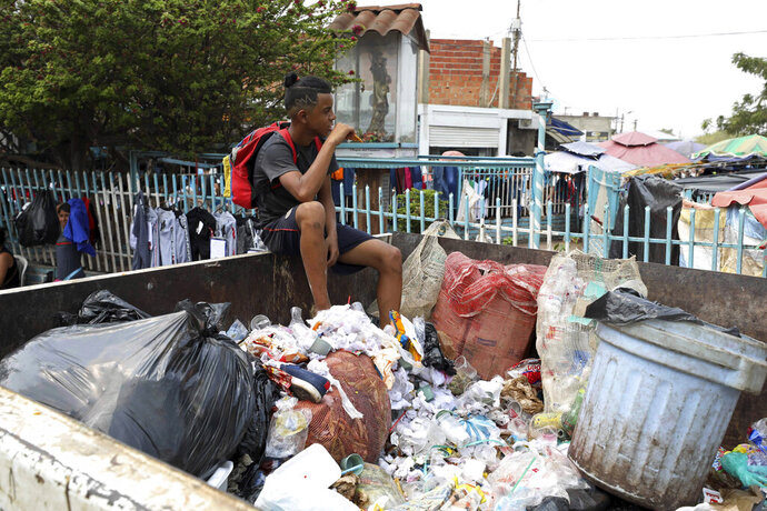 A Venezuelan youth pauses from searching through a trash bin in La Parada, on the outskirts of Cucuta, Colombia, on the border with Venezuela, Monday, Feb. 4, 2019. Venezuelan opposition leader Juan Guaido is moving ahead with plans to try to bring in humanitarian aid through the Colombian border city of Cucuta, where the U.S. government will transport and store food and medical supplies destined for Venezuela. (AP Photo/Fernando Vergara)
