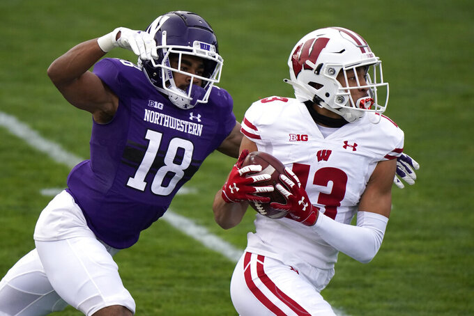 Wisconsin wide receiver Chimere Dike, right, runs for a touchdown after catching a pass against Northwestern defensive back Cameron Ruiz during the first half of an NCAA college football game in Evanston, Ill., Saturday, Nov. 21, 2020. (AP Photo/Nam Y. Huh)