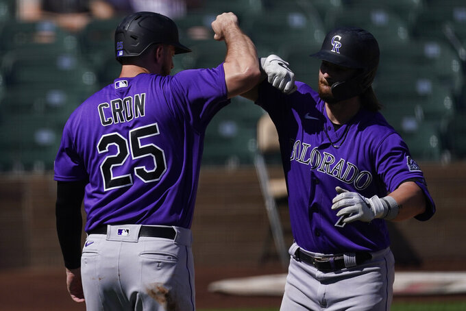 Colorado Rockies' Brendan Rodgers, right, celebrates with C.J. Chron (25) after they both scored off of a home run hit by Rodgers during the first inning of a spring training baseball game against the Arizona Diamondbacks Tuesday, March 9, 2021, in Scottsdale, Ariz. (AP Photo/Ashley Landis)