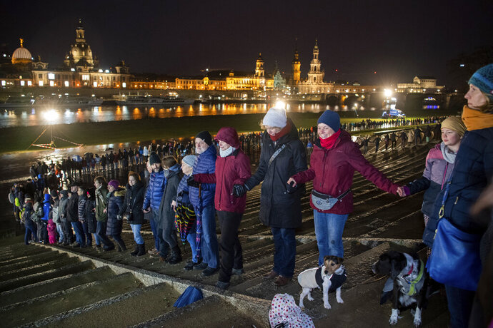People form a human chain on the banks of the Elbe river with the historical old town in background, marking the 75th anniversary of the destruction of Dresden in the Second World War, in Dresden, Germany, Thursday Feb. 13, 2020.  A 1945 allied bombing campaign reduced the centre of Dresden to rubble leaving about 25,000 people dead. (Robert Michael/dpa via AP)