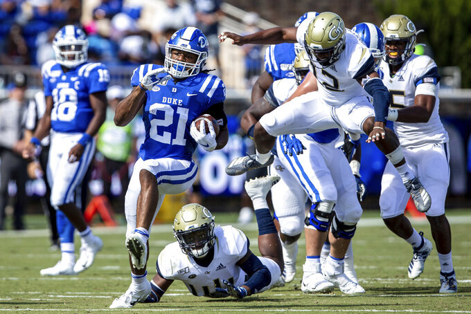 Duke's Mateo Durant (21) carries the ball past Georgia Tech's Bruce Jordan-Swilling (12) and Quez Jackson (44) during an NCAA college football game in Durham, N.C., Saturday, Oct. 12, 2019. (AP Photo/Ben McKeown)