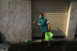 Maria Del Carmen Pineda Gomez, who says she is suffering from a respiratory infection that began three days earlier, wears a mask to protect herself against air pollution as she cleans a storefront on pedestrian Madero Street in the historic center of Mexico City, Thursday, May 16, 2019. A siege of air pollution blanketing the capital has led to school closures and the cancellation of professional sporting events.(AP Photo/Rebecca Blackwell)