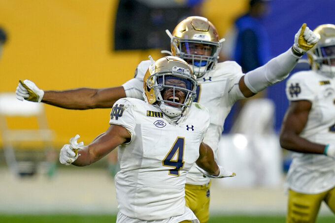 Notre Dame cornerback Nick McCloud (4) celebrates in front of safety Houston Griffith (3) after intercepting a pass during the second half of an NCAA college football game, Saturday, Oct. 24, 2020, in Pittsburgh. Notre Dame won 45-3. (AP Photo/Keith Srakocic)