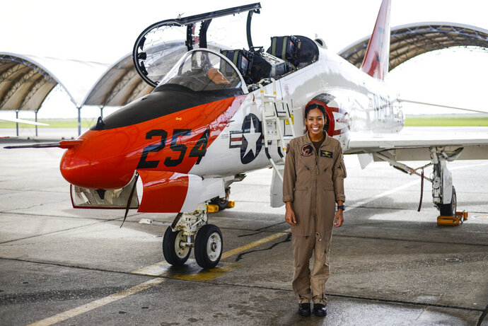 In this photo provided by the U.S. Navy, student Naval aviator Lt. j.g. Madeline Swegle, assigned to the Redhawks of Training Squadron (VT) 21 at Naval Air Station Kingsville, Texas, stands by a T-45C Goshawk training aircraft following her final flight to complete the undergraduate Tactical Air (Strike) pilot training syllabus, July 7, 2020, in Kingsville, Texas. Swegle is the Navy's first known Black female strike aviator and will receive her Wings of Gold during a ceremony on July 31. (Lt.j.g. Luke Redito/U.S. Navy via AP)