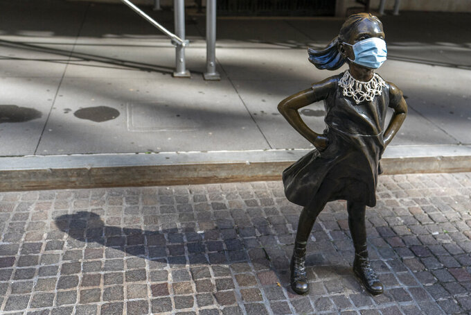 A face mask and a Ruth Bader Ginsberg collar is placed on The Fearless Girl statue during the Women's March outside the New York Stock Exchange, Saturday, Oct. 17, 2020, in New York. Dozens of Women's March rallies were planned from New York to San Francisco to signal opposition to President Donald Trump and his policies, including the push to fill the seat of late Supreme Court Justice Ruth Bader Ginsburg before Election Day. (AP Photo/Mary Altaffer)