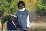 FILE - In this Sunday, July, 29, 2018, file photo, Former Zimbabwean President Robert Mugabe, left, and his wife Grace pose for a photo after a press conference at their residence in Harare. On Friday, Sept. 6, 2019, Zimbabwe President Emmerson Mnangagwa said his predecessor Robert Mugabe, age 95, has died. (AP Photo/Tsvangirayi Mukwazhi, File)