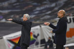 Tottenham's manager Jose Mourinho, left, and Manchester City's head coach Pep Guardiola give instructions from the side line during the English Premier League soccer match between Tottenham Hotspur and Manchester City at Tottenham Hotspur Stadium in London, England, Saturday, Nov. 21, 2020. (Neil Hall/Pool via AP)