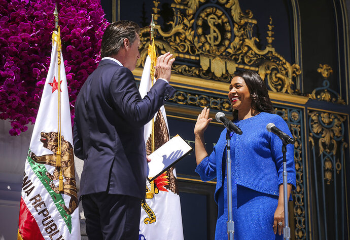 California Lt. Gov. Gavin Newsom, left, swears in London Breed as San Francisco's new mayor, outside City Hall, Wednesday, July 11, 2018, in San Francisco. Breed, the first African-American female mayor of San Francisco, made history as she took the oath of office, vowing to help drug users and the homeless in a city that has come to embody extreme wealth and poverty. (Gabrielle Lurie/San Francisco Chronicle via AP, Pool)