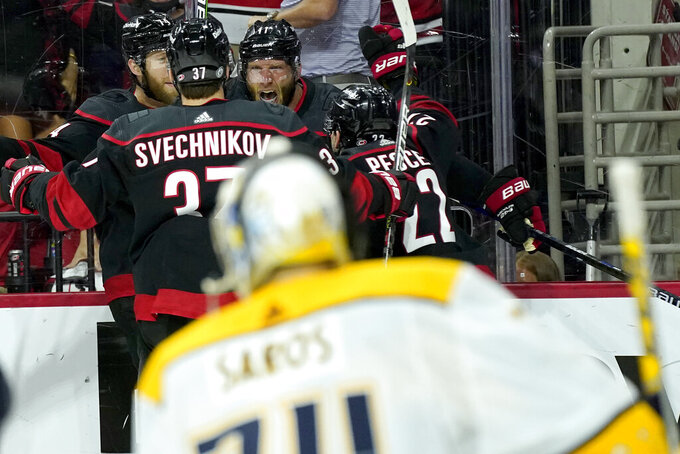 Carolina Hurricanes center Jordan Staal (11) celebrates with right wing Andrei Svechnikov (37), defenseman Jaccob Slavin (74) and defenseman Brett Pesce (22) after Staal scored in overtime against the Nashville Predators during Game 5 of an NHL hockey Stanley Cup first-round playoff series in Raleigh, N.C., Tuesday, May 25, 2021. (AP Photo/Gerry Broome)