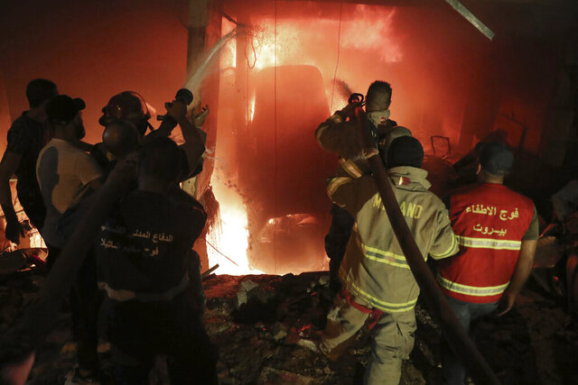 Firefighters extinguish a fire at a building  after a diesel tank exploded in the neighborhood of Tarik al-Jadida, in Beirut, Lebanon, Friday, Oct. 9, 2020. (AP Photo/Bilal Hussein)