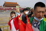 A woman lowers her mask for a selfie on Tiananmen Square during National Day in Beijing on Thursday, Oct. 1, 2020. Millions of Chinese tourists usually would use their week-long National Day holidays to travel abroad. This year, travel restrictions due to the coronavirus pandemic mean that some 600 million tourists - about 40% of the population - will travel within China during the holiday that began Thursday, according to Ctrip, China's largest online travel agency. (AP Photo/Ng Han Guan)