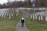 A woman walks through the cemetery of the Potocari memorial center for victims of the Srebrenica genocide in Potocari, Bosnia and Herzegovina, Wednesday, March 20, 2019. United Nations appeals judges on Wednesday upheld the convictions of former Bosnian Serb leader Radovan Karadzic for genocide, war crimes and crimes against humanity, and increased his sentence from 40 years to life imprisonment. (AP Photo/Marko Drobnjakovic)