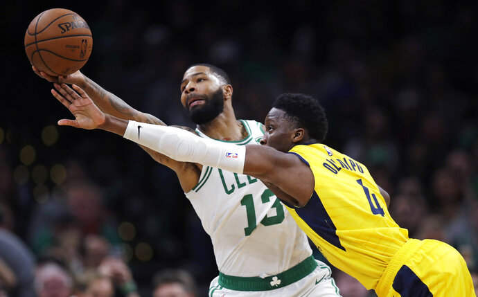 Boston Celtics forward Marcus Morris (13) grabs a pass against Indiana Pacers guard Victor Oladipo (4) during the second half of an NBA basketball game in Boston, Wednesday, Jan. 9, 2019. The Celtics defeated the Pacers 135-108. (AP Photo/Charles Krupa)