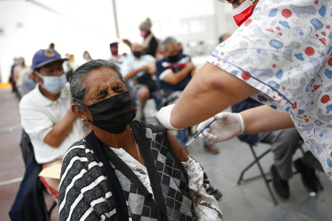 Maria Castrejon, 71, grimaces as she is vaccinated with a second dose of the Sinovac COVID-19 vaccine at the Americas Cultural Center, in Ecatepec, Mexico, Saturday, April 3, 2021. (AP Photo/Ginnette Riquelme)