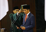 Indonesian President Joko Widodo, right, reads his oath during his inauguration ceremony as the country's seventh president at the parliament building in Jakarta, Indonesia Sunday, Oct. 20, 2019. Widodo, who rose from poverty and pledged to champion democracy, fight entrenched corruption and modernize the world's most populous Muslim-majority nation, was sworn in Sunday for his second and final five-year term with a pledge to take bolder actions. (AP Photo/Achmad Ibrahim, Pool)