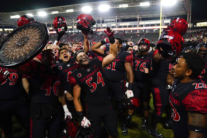San Diego State players celebrate a 33-31 win in triple overtime against Utah in an NCAA college football game Saturday, Sept. 18, 2021, in Carson, Calif. (AP Photo/Ashley Landis)