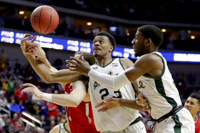 Bradley's Luuk van Bree, left, competes for a rebound against Michigan State's Xavier Tillman (23) and Aaron Henry, right, during the second half of a first round men's college basketball game in the NCAA Tournament in Des Moines, Iowa, Thursday, March 21, 2019. (AP Photo/Nati Harnik)
