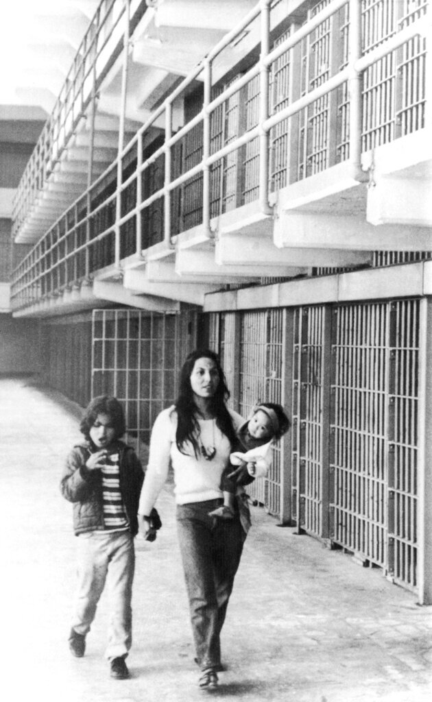 In this photo taken March 26, 1970, Eldy Bratt, 33, walks down the lonely corridor of a cell block on Alcatraz with her son Peter Bratt, left, and one of her daughters in San Francisco. The week of Nov. 18, 2019, marks 50 years since the beginning of a months-long Native American occupation at Alcatraz Island in the San Francisco Bay. The demonstration by dozens of tribal members had lasting effects for tribes, raising awareness of life on and off reservations, galvanizing activists and spurring a shift in federal policy toward self-determination. (AP Photo/Richard Drew, File)