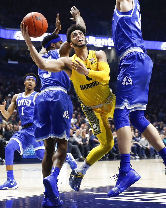 Marquette's Markus Howard, center, shoots between Xavier's Quentin Goodin, left, and Zach Hankins, right, in the second half of an NCAA college basketball game, Saturday, Jan. 26, 2019, in Cincinnati. (AP Photo/John Minchillo)
