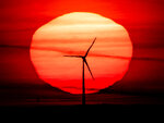 The sun rises behind a wind turbine in Frankfurt, Germany, early Tuesday, Sept. 15, 2020. (AP Photo/Michael Probst)