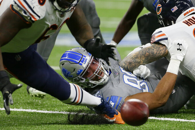 Detroit Lions defensive end Romeo Okwara looks back as Chicago Bears offensive guard Rashaad Coward reaches for the loose ball during the first half of an NFL football game, Thursday, Nov. 28, 2019, in Detroit. (AP Photo/Duane Bureson)