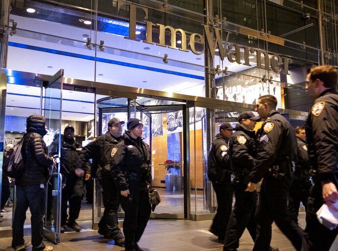 After the building was determined safe, New York City police officers walk from the Time Warner Center in New York Thursday, Dec. 6, 2018, after a bomb threat was called into the building and occupants were evacuated, including CNN employees. (AP Photo/Craig Ruttle)