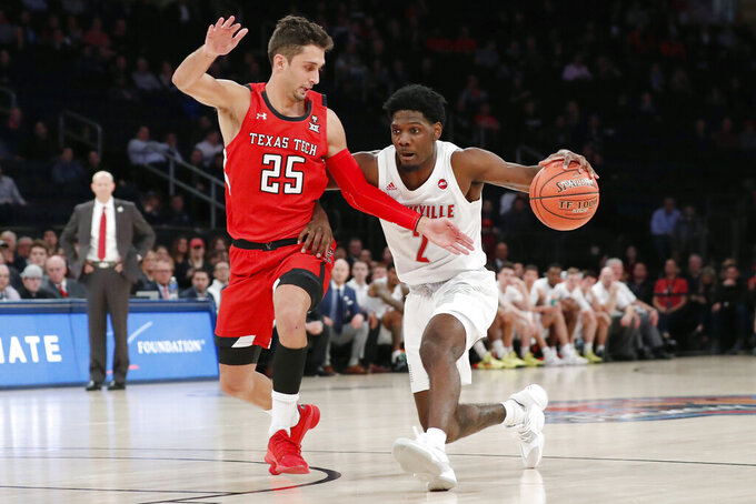 Texas Tech guard Davide Moretti (25) defends Louisville guard Darius Perry (2) as he drives down the court during the first half of an NCAA college basketball game in the Jimmy V Classic, Tuesday, Dec. 10, 2019, in New York. (AP Photo/Kathy Willens)