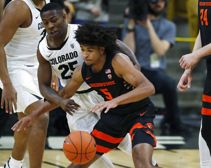 Oregon State guard Ethan Thompson, front, struggles to pull in the ball as Colorado guard McKinley Wright IV defends in the second half of an NCAA college basketball game Sunday, Jan. 5, 2020, in Boulder, Colo. (AP Photo/David Zalubowski)