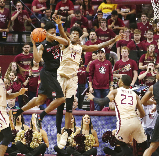 North Carolina State's CJ Bryce, left, tries to get around the defense of Florida State's Terance Mann in the second half of an NCAA college basketball game Saturday, March 2, 2019, in Tallahassee, Fla. Florida State won 78-73. (AP Photo/Steve Cannon)