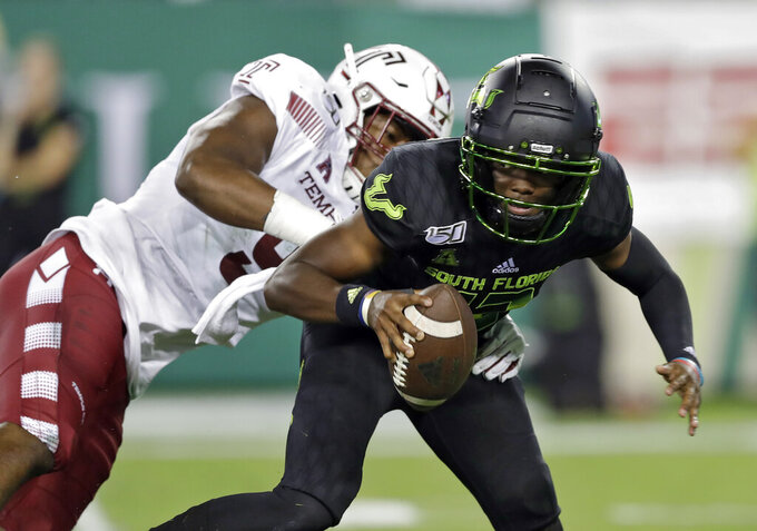File-This Nov. 7, 2019, file photo shows South Florida quarterback Jordan McCloud (12) eluding a sack by Temple defensive end Quincy Roche during the first half of an NCAA college football game in Tampa, Fla. Roche was named American Athletic Conference Defensive Player of the Year after ringing up 13 sacks, including 10 in the Owls' final four games. In a pivotal victory over then No. 21 Maryland, the 6-foot-4, 235-pounder had a sack, a blocked kick and six tackles. (AP Photo/Chris O'Meara, File)