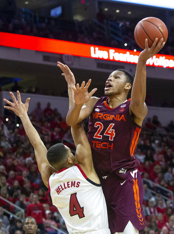 Virginia Tech's Kerry Blackshear Jr. (24) attempts a shot over North Carolina State's Jericole Hellems (4) during the second half of an NCAA college basketball game in Raleigh, N.C., Saturday, Feb. 2, 2019. (AP Photo/Ben McKeown)