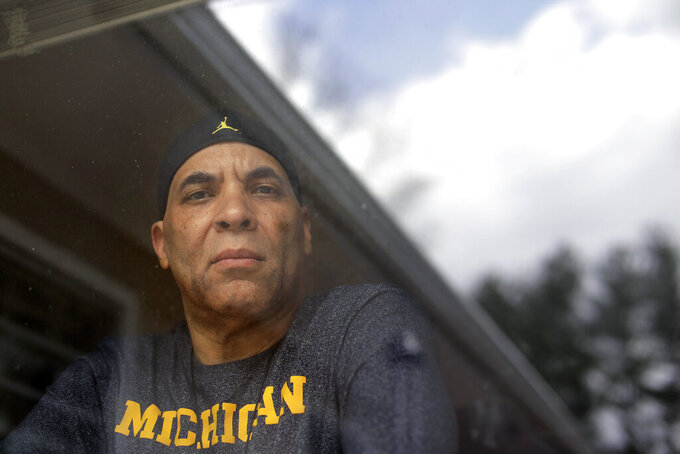 Chuck Christian, of Randolph, Mass., the first former Michigan football player to publicly say that a team doctor abused him, looks through a window in his home while standing for a photograph, Wednesday, April 22, 2020, in Randolph. Christian, a 60-year-old artist, said during a videoconferencing interview Wednesday, April 22, that the late Dr. Robert Anderson gave him unnecessary rectal exams before he played for the Wolverines during 1977-80 seasons. (AP Photo/Steven Senne)