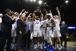 Hofstra guard Jalen Ray (20) and others raise the trophy after an NCAA college basketball game against Northeastern for the championship of the Colonial Athletic Association men's tournament Tuesday, March 10, 2020, in Washington. (AP Photo/Nick Wass)