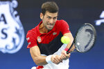 Novak Djokovic of Serbia plays a shot during his match against Cristian Garin of Chile at the ATP Cup tennis tournament in Brisbane, Australia, Wednesday, Jan. 8, 2020. (AP Photo/Tertius Pickard)