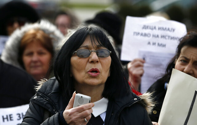 In this photo taken Monday, Feb. 24, 2020, Mirjana Novokmet speaks during a protest in front of the parliament building in Belgrade, Serbia. After years of waiting, Serbian lawmakers are set to soon pass a bill that authorities say attempts to shed light on a chilling, decades-old scandal involving hundreds of families who suspect their babies were stolen at birth. Mirjana Novokmet does not believe that this special law will help uncover what happened to her first child back in 1978. (AP Photo/Darko Vojinovic)