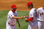 Los Angeles Angels pitcher Shohei Ohtani, right, of Japan, is taken our of the baseball game by manager Joe Maddon during the second inning against the Houston Astros on Sunday, Aug. 2, 2020, in Anaheim, Calif. (AP Photo/Mark J. Terrill)