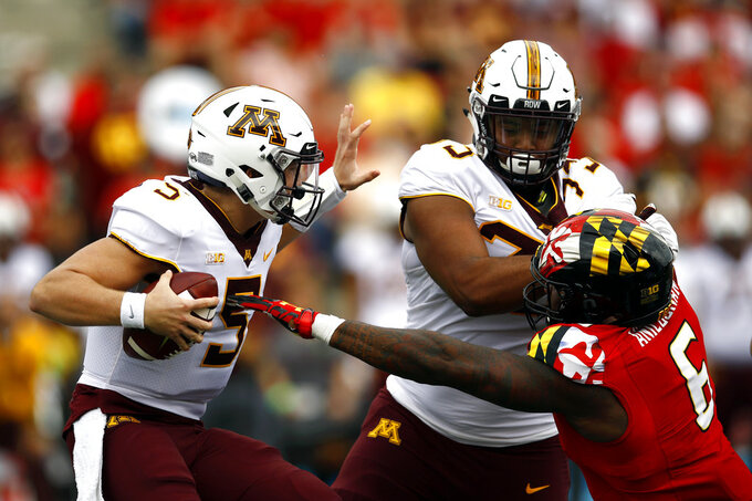 FILE - In this Sept. 22, 2018, file photo, Minnesota quarterback Zack Annexstad, left, protects the ball as offensive lineman Donnell Greene, second from right, tries to keep Maryland defensive lineman Jesse Aniebonam away in the first half of an NCAA college football game, in College Park, Md. The Terrapins average a Big Ten-best 6.19 yards per carry. Michigan is allowing 86 yards on the ground and limiting opponents to 2.37 yards per carry. Maryland plays at Michigan on Saturday, Oct. 6. (AP Photo/Patrick Semansky, File)