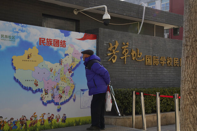 An elderly Chinese man looks at map of Chinese showing its different ethnic groups and the slogan
