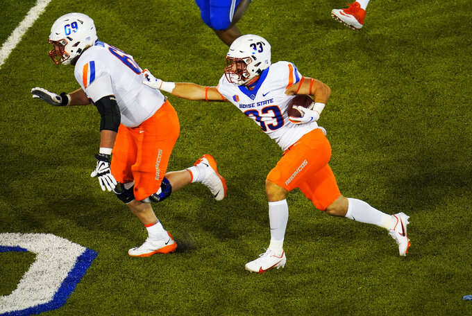 Boise State offensive lineman Garrett Curran, left, leads the way for a short gain for running back Tyler Crowe in the second half of an NCAA college football game against Air Force, Saturday, Oct. 31, 2020, at Air Force Academy, Colo. (AP Photo/David Zalubowski)