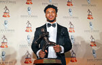 Heisman Trophy winner quarterback Kyler Murray posses with the Davey O'Brien football award he received in Fort Worth, Texas, Monday, Feb. 18, 2019. Murray accepted the Davey O'Brien award in his first public appearance since the Heisman Trophy winner announced his plan to pursue an NFL career rather than report to spring training as a first-round pick of the Oakland A's. (AP Photo/LM Otero)