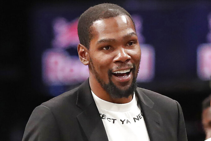 FILE - In this Dec. 26, 2019, file photo, injured Brooklyn Nets player Kevin Durant smiles as he greets teammates returning to the bench during a timeout in the second half of an NBA basketball game against the New York Knicks, in New York. Brooklyn Nets forward Kevin Durant has joined the ownership group of Major League Soccer's Philadelphia Union. Durant, a 10-time NBA All-Star, has a 5% ownership stake, with an option for 5% more in the near future, the Union announced Monday, June 15, 2020. (AP Photo/Kathy Willens, File)